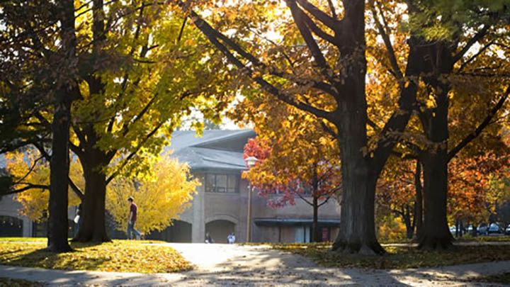 Photograph of Spoelhof Center through trees with orange and yellow leaves.