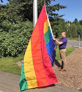 Student Diversity Center director Miguel Macias prepares the Rainbow Pride flag to be raised on campus.