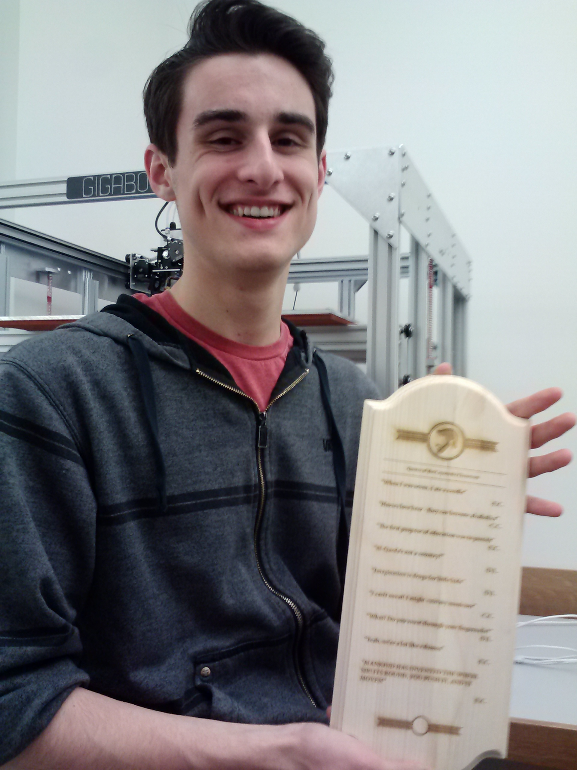Photograph of the a student holding up a wood plaque they engraved