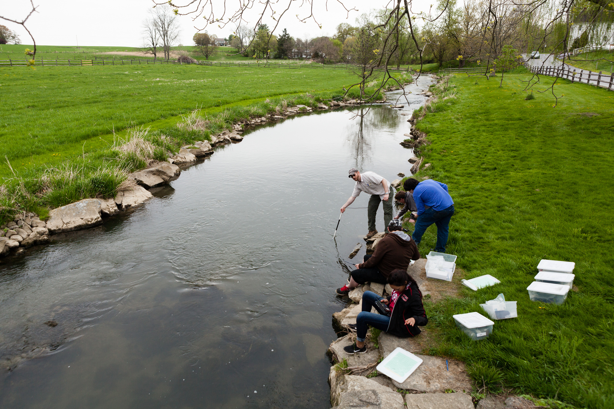 Image of five people sitting on the edge of a stream, testing the water quality.