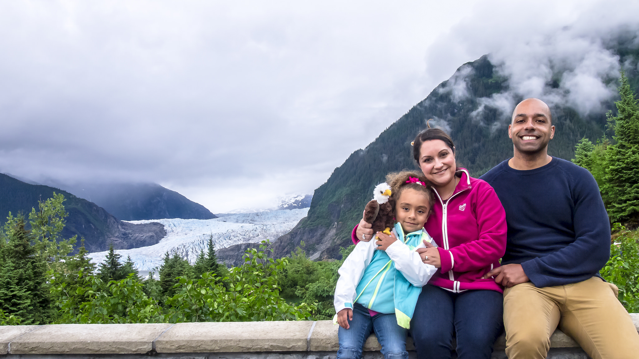 Image of two parents and a young girl in front of a glacier in Alaska.