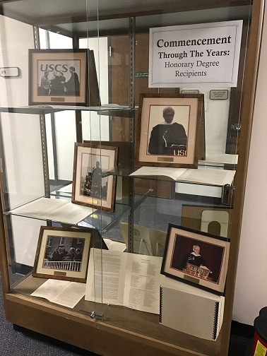 Image of Honorary Degree Recipient exhibit, consisting of five framed photographs and graduation programs providing information on the recipients, housed in an upright display case with four staggered shelves..