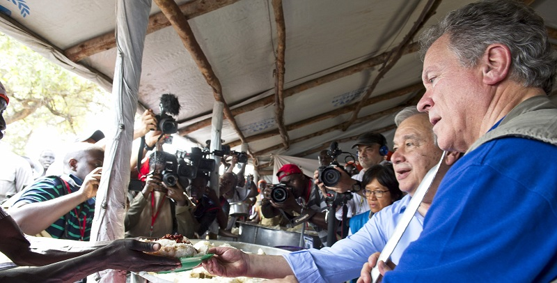 Secretary-General António Guterres and WFP Executive Director David Beasley serving meals for newly arrived refugees in Uganda; UN Photo 727022