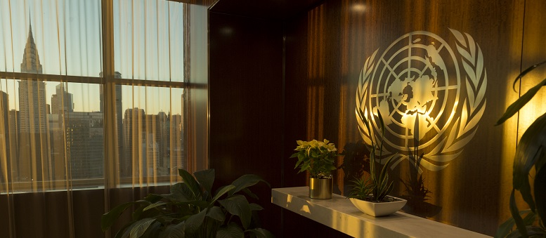 UN emblem and city skyline in afternoon light, UN Photo 744496