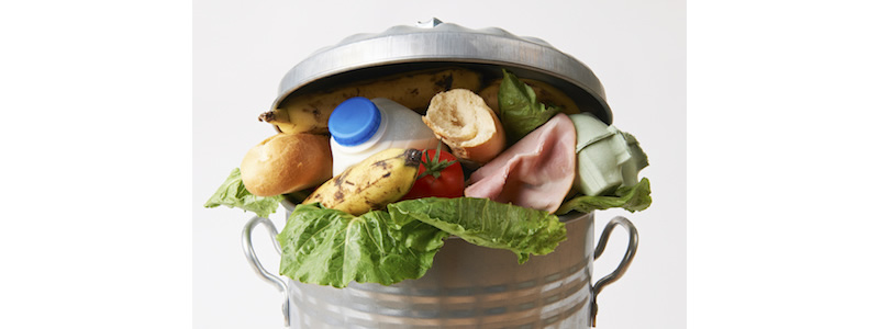 Trashcan over-filled with edible food items.