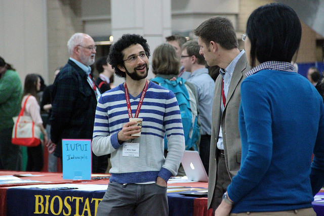 a man in front of a table at a graduate orientation fair talking with a prospective student, while another student looks on