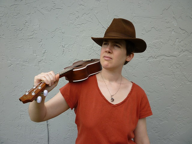 young person wearing a hat and holding ukulele over the shoulder