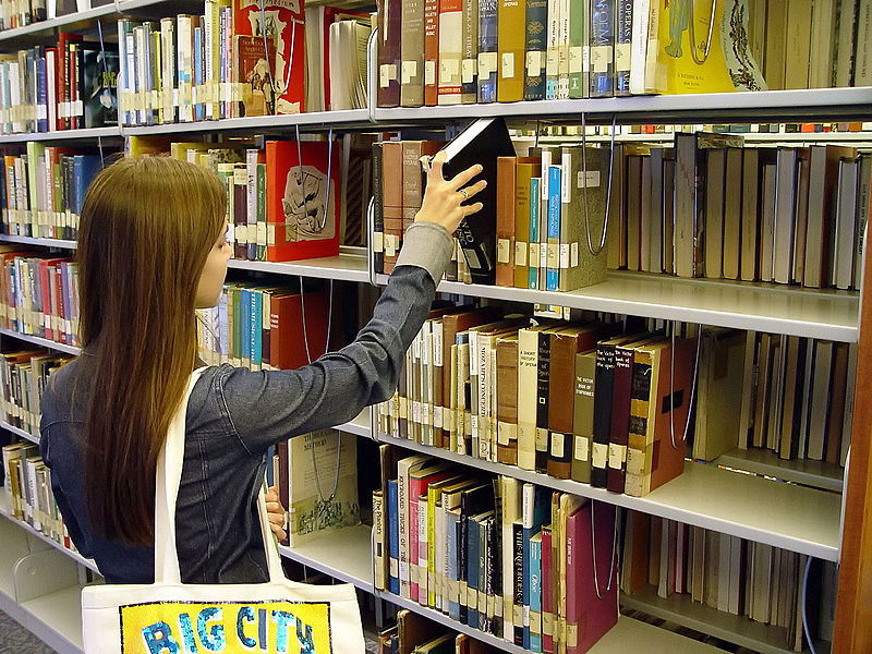 Student pulling books from shelf