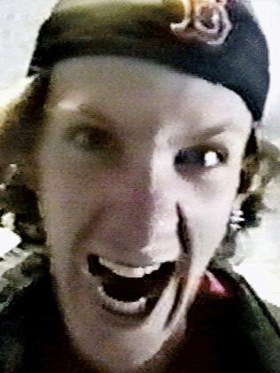 Photograph of Dylan Klebold's face with his mouth open and teeth exposed in an exaggerated aggressive expression.