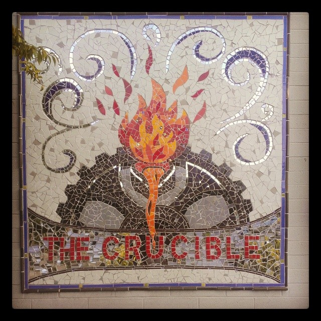 "Mosaic on a wall. The words ""The Crucible"" are at the bottom. Half a gear is above it with a torch in front."