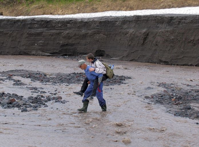 Person being carried by another through muddy waters.