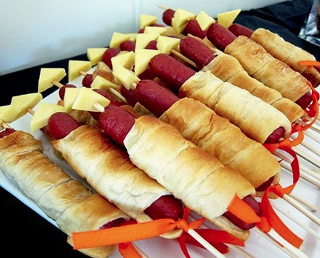Hot dogs wrapped in dough on a stick with cheese on the end.