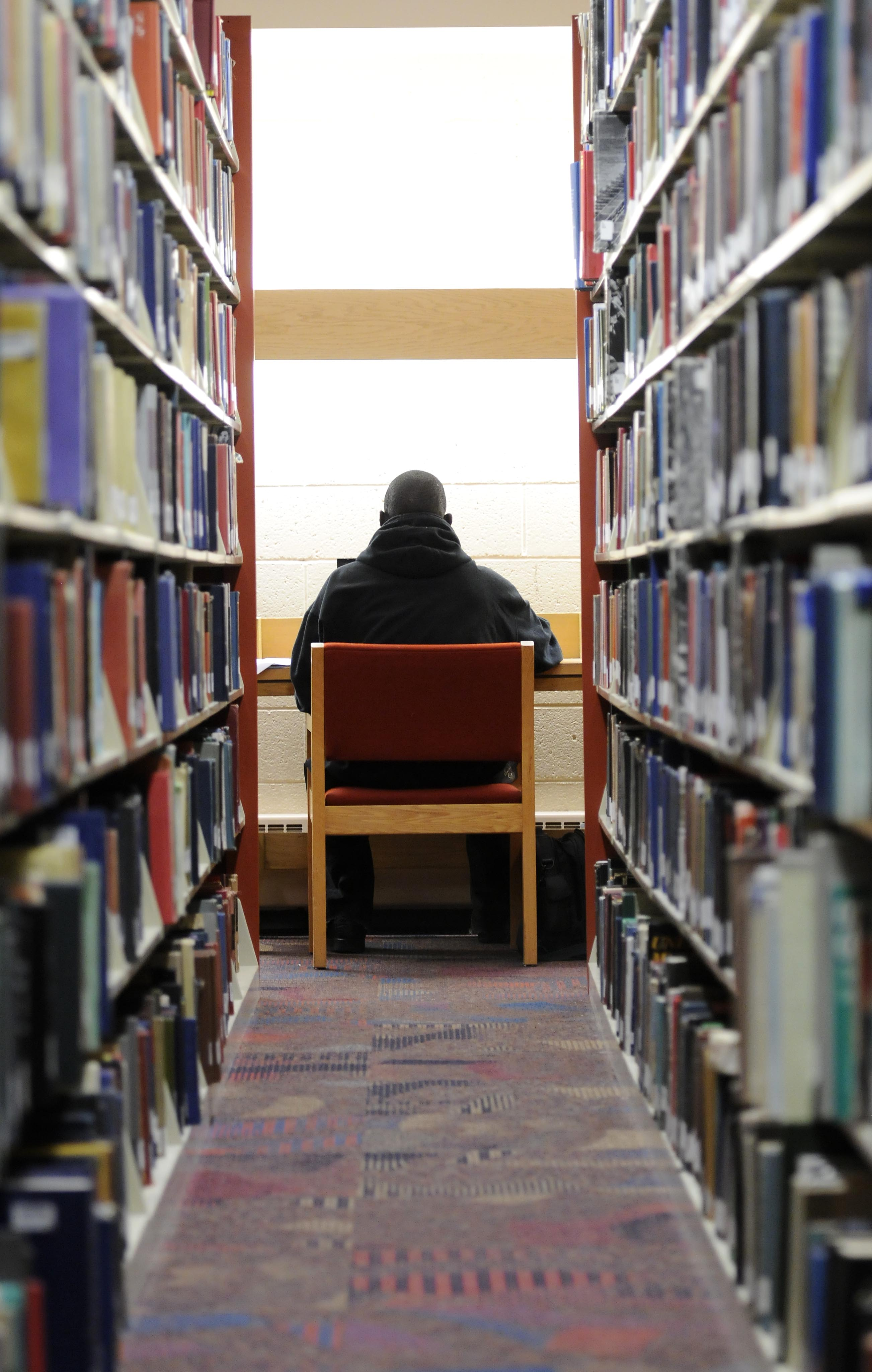 The back of a library user working at a table in the library stacks.