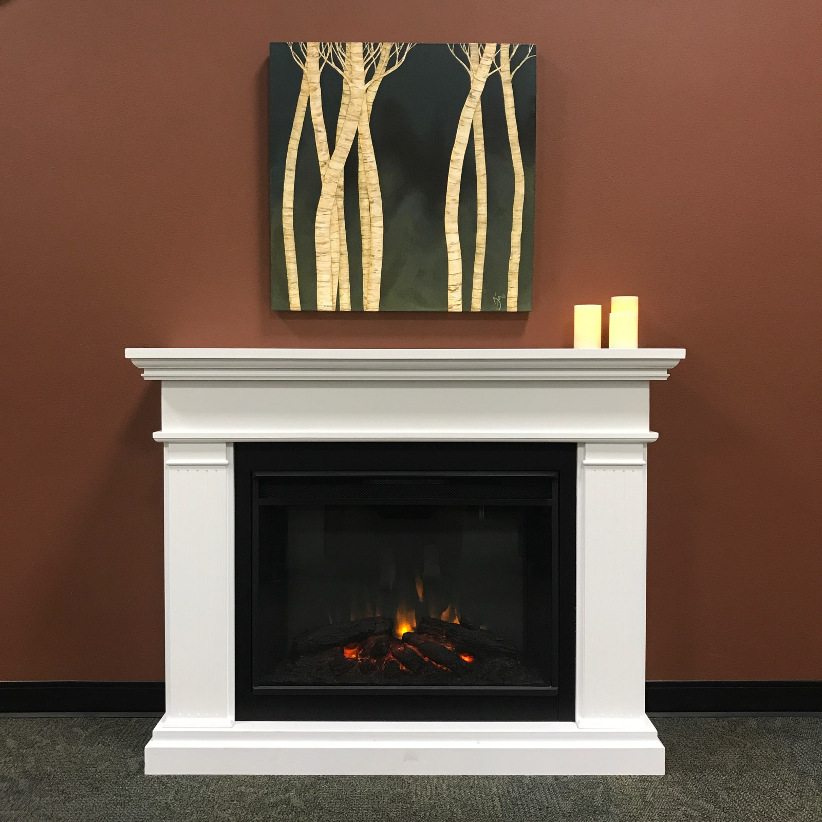 Library fireplace with birch tree painting above it.