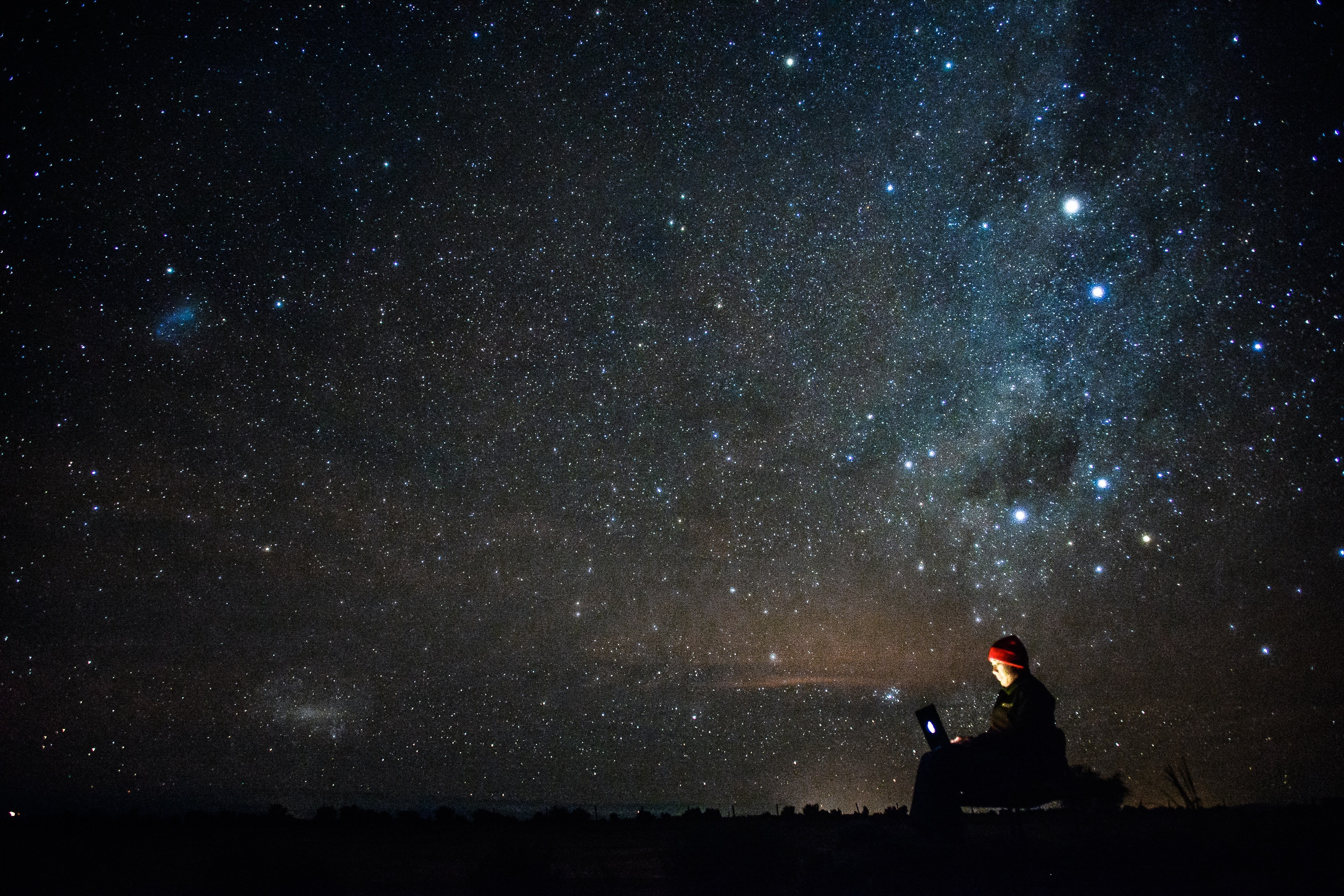 Person sitting under the stars with laptop.