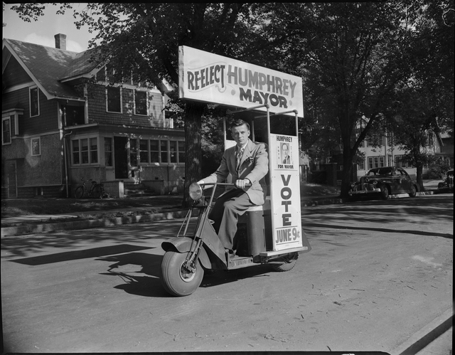 Hubert Humphrey for mayor campaign worker riding his Cushman scooter around before the election