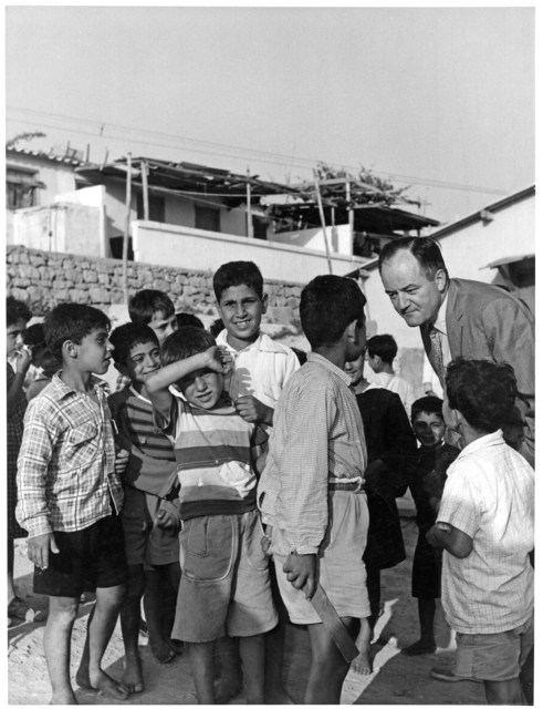 Senator Hubert H. Humphrey enjoying a visit with children in a Palestinian refugee camp on the outskirts of Beirut