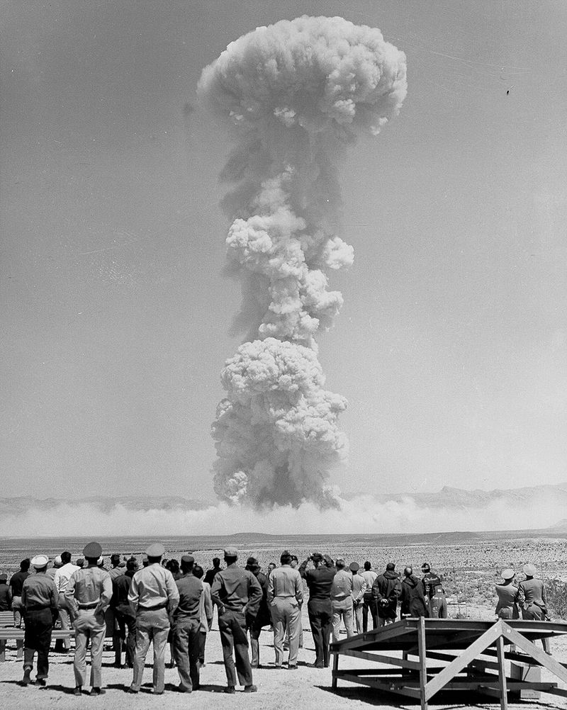 Image of men in uniforms watching mushroom cloud which seems far too close. Operation Teapot