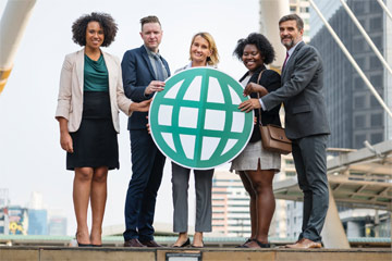 five business people holding a cardboard globe cutout