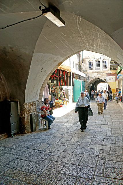 Archway in Jerusalem with woman in traditional Arab dress.