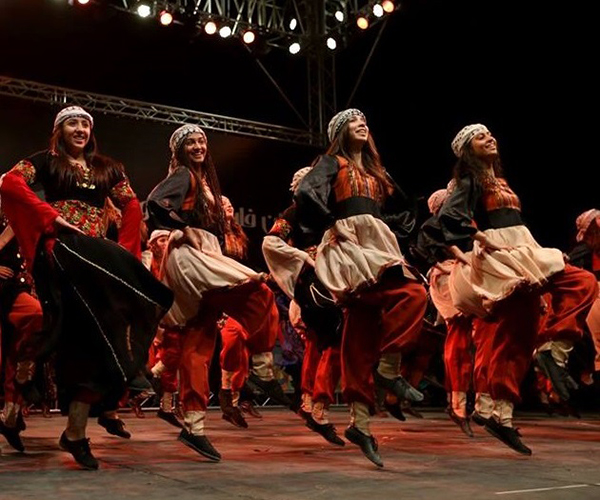 Four girls dancing in traditional Palestinian costume.