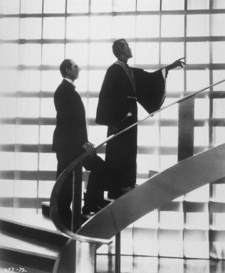 Bela Lugosi and Boris Karloff walking up staircase in front of glass block wall.