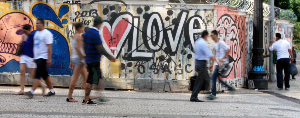 pedestrians walking by a wall with grafitti and the word love
