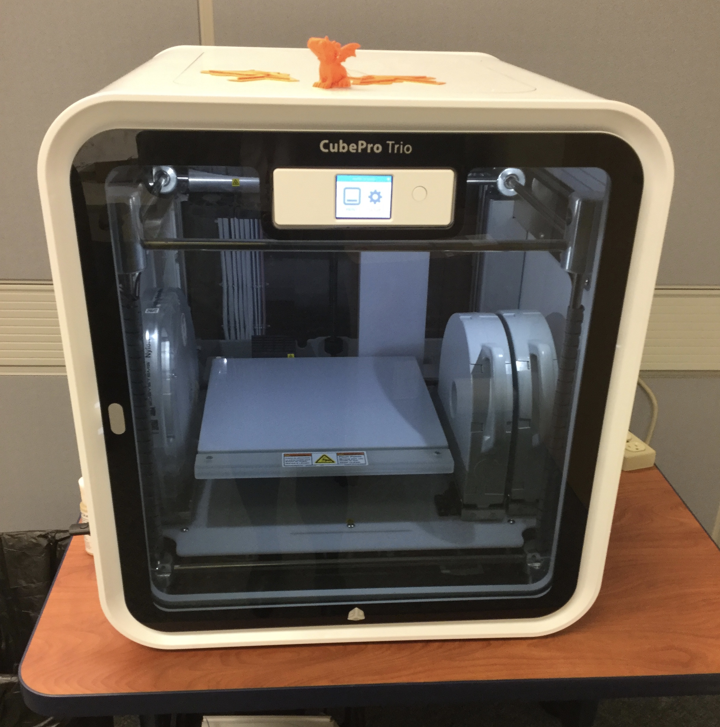 A picture of a CubePro trio 3D printer--a 2.5 foot square white plastic box with rounded edges and a grey transparent front door, through which the inner mechanism can be seen. On top is a small orange 3D printed dragon, named Percy.