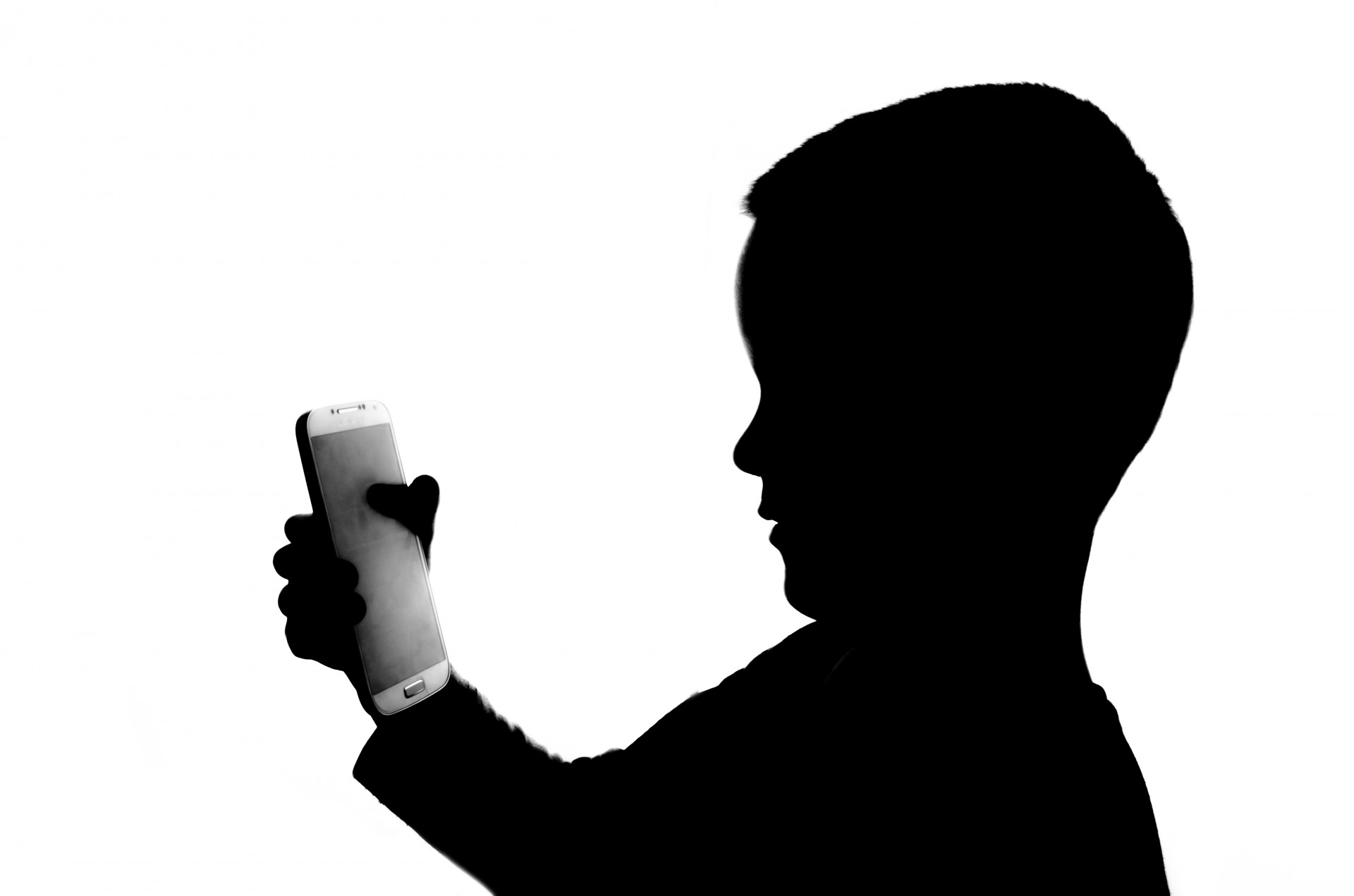 silhouette of boy holding cell phone