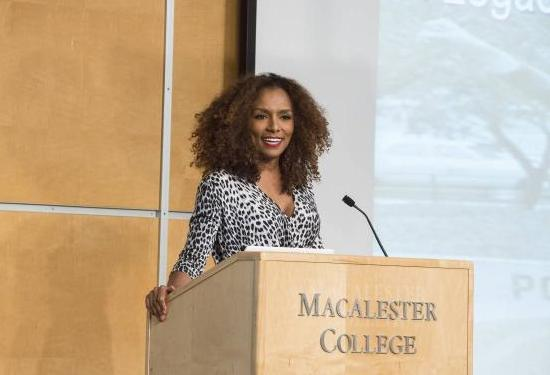 Image: Janet Mock standing at a podium with the words Macalester College on it