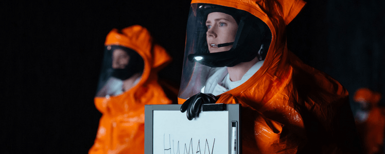 "Amy Adams in Arrival with sign that says ""human"""