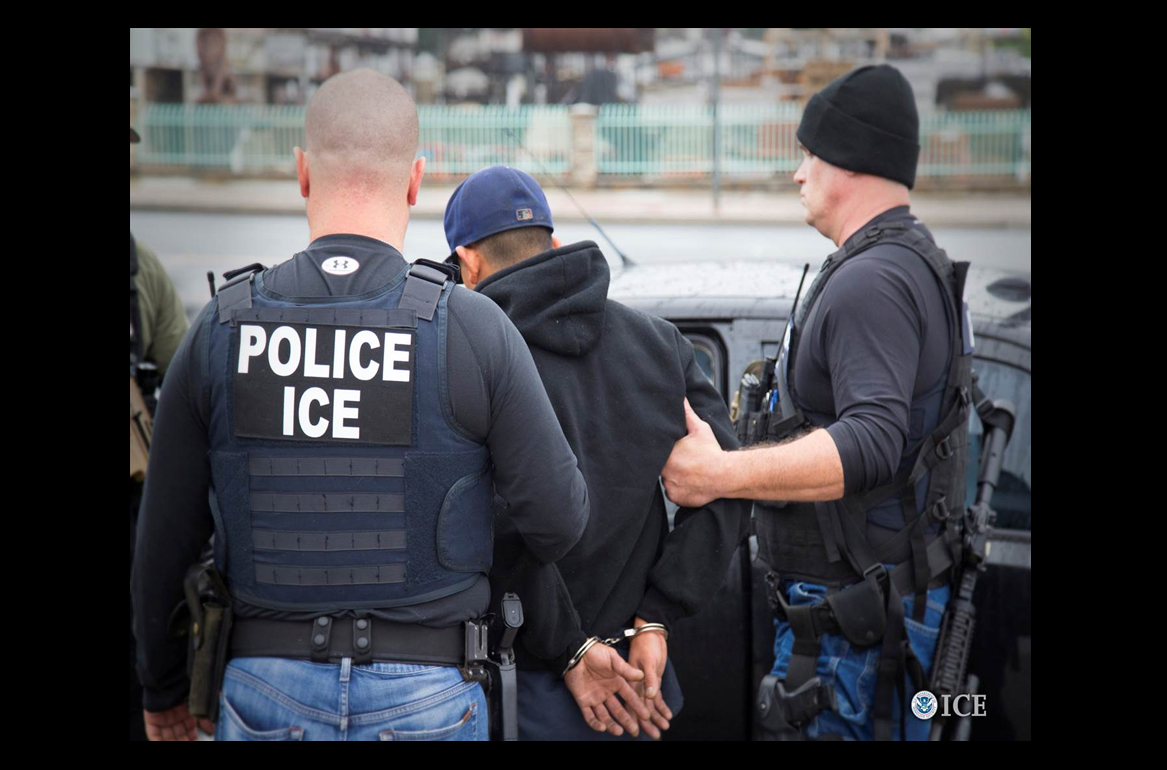 Two ICE police officers detain a suspect in handcuffs