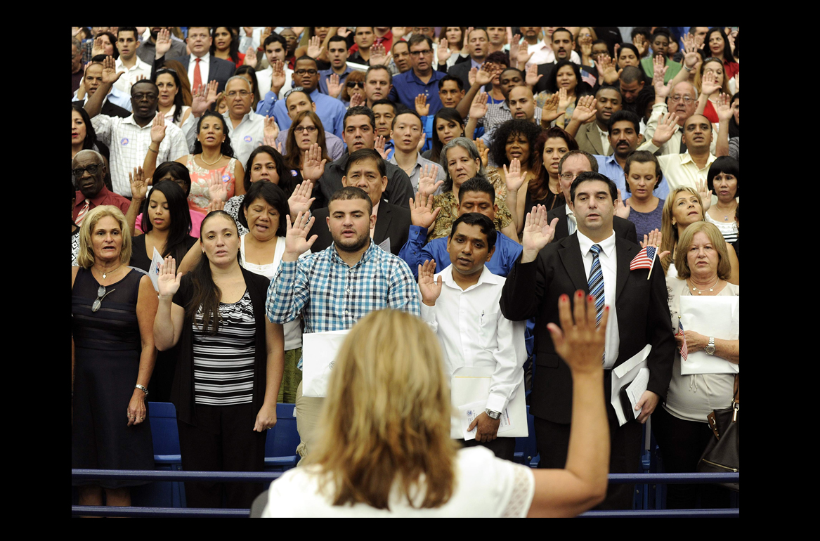 A large group of people all holding their right hands up and reciting the Oath of Allegiance