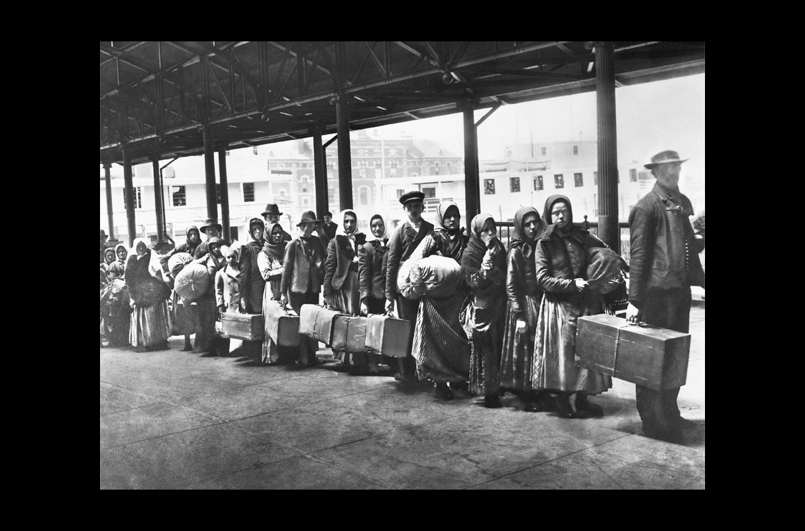 A black and white photograph showing immigrants waiting on line and holding suitcases.