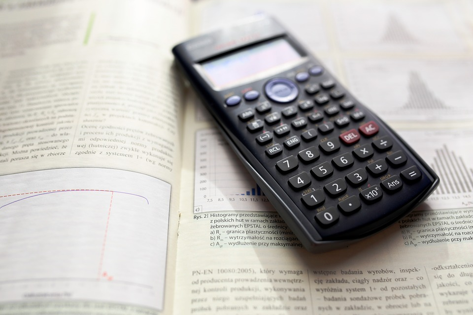 A calculator atop a math book