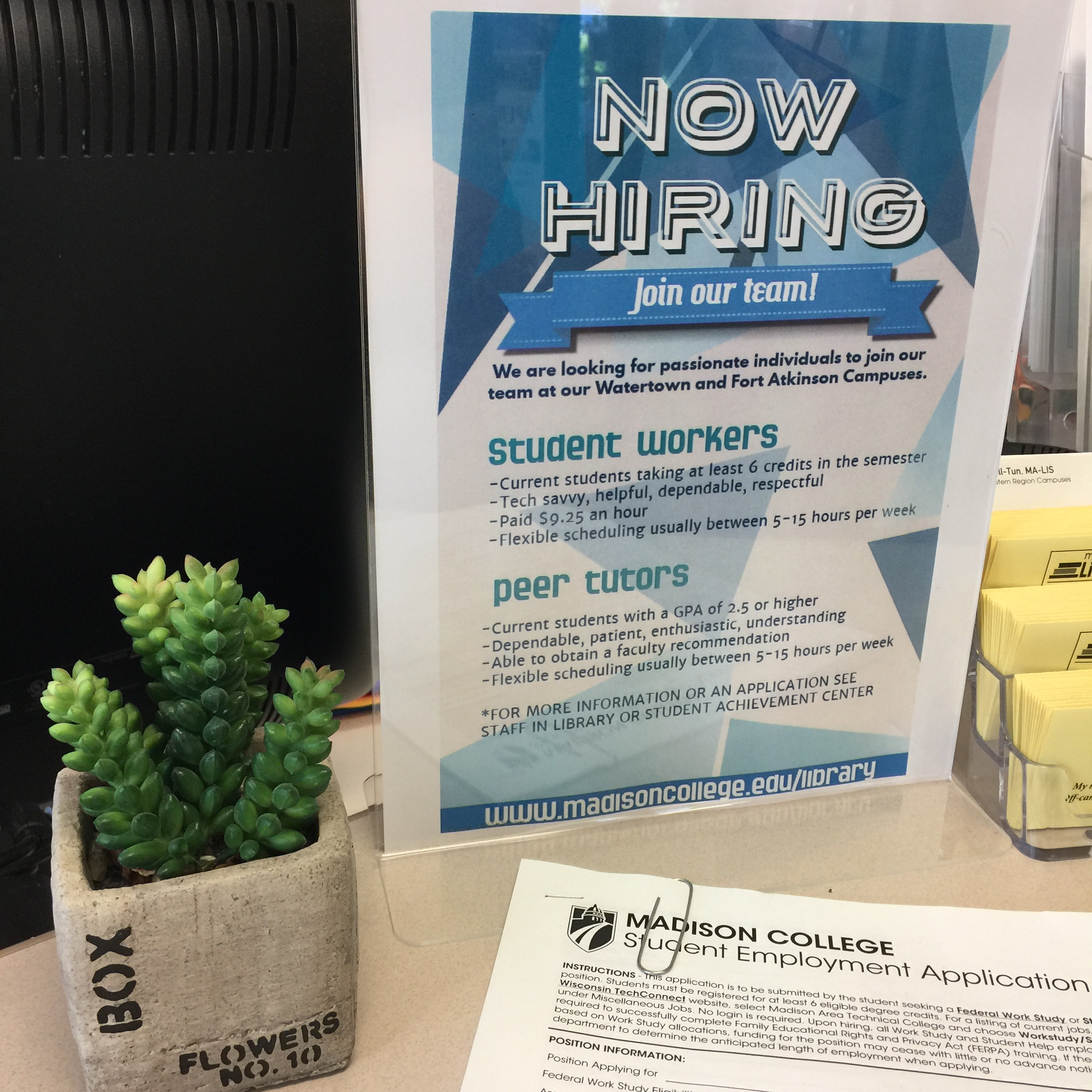 Now Hiring sign with plant