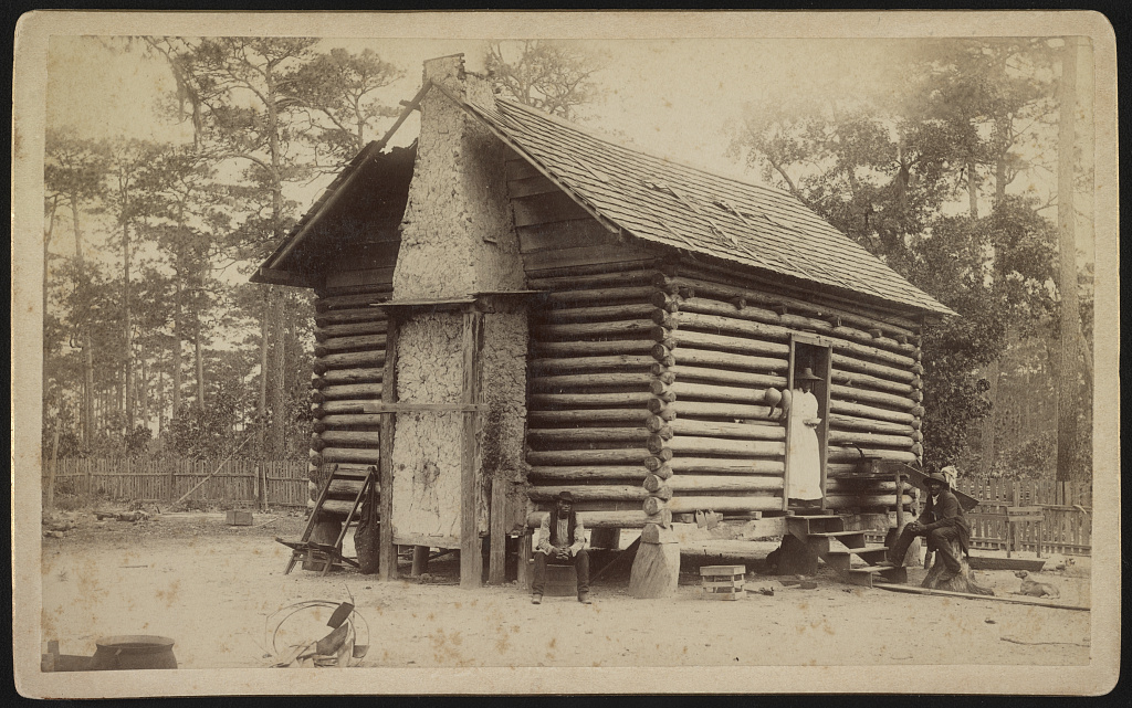 a log cabin with two African American men seated outside and an African American woman standing in the doorway