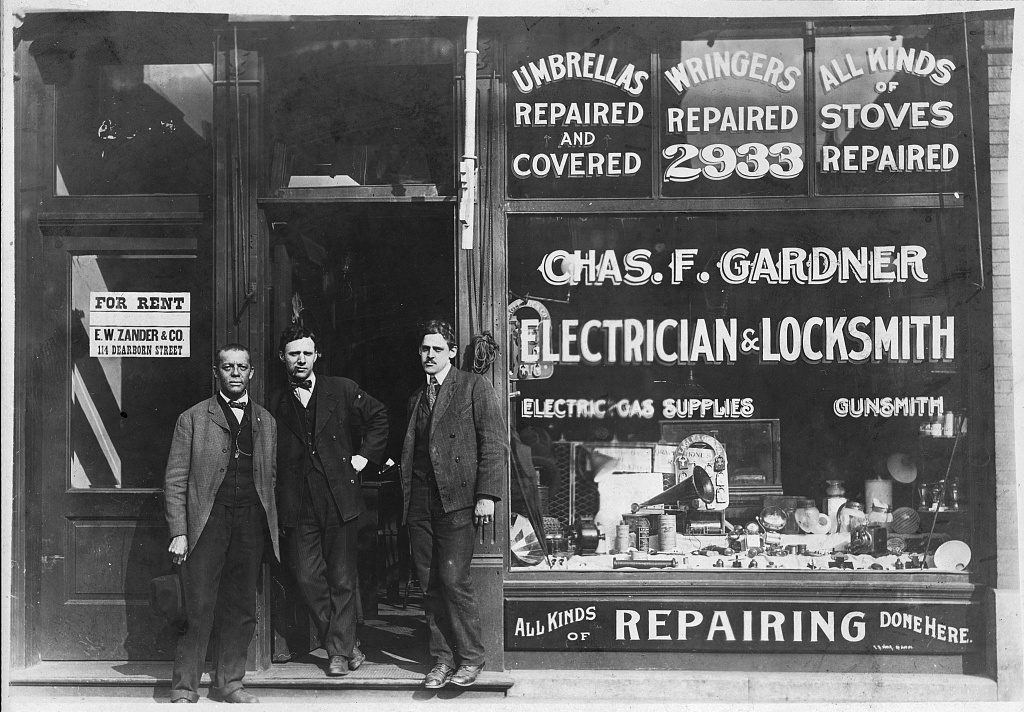 "three men standing at the entrance to the business establishment of ""Chas. F. Gardner Electrician and Locksmith"""