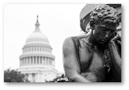 U.S. Capitol building in the background with a statue of a man in a thinking pose in the foreground.