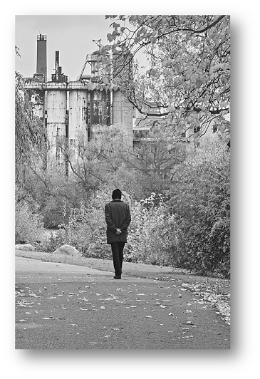 Black and whit image of a man walking in a park.