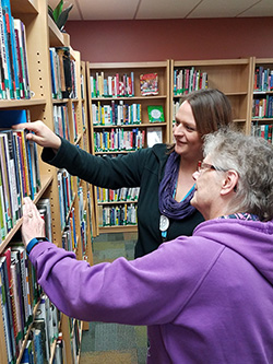 Librarian helping patron find a book