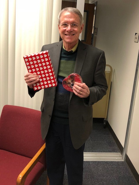 photo of Dr. Gibson, Provost for Southeast campus, holding his book and candy