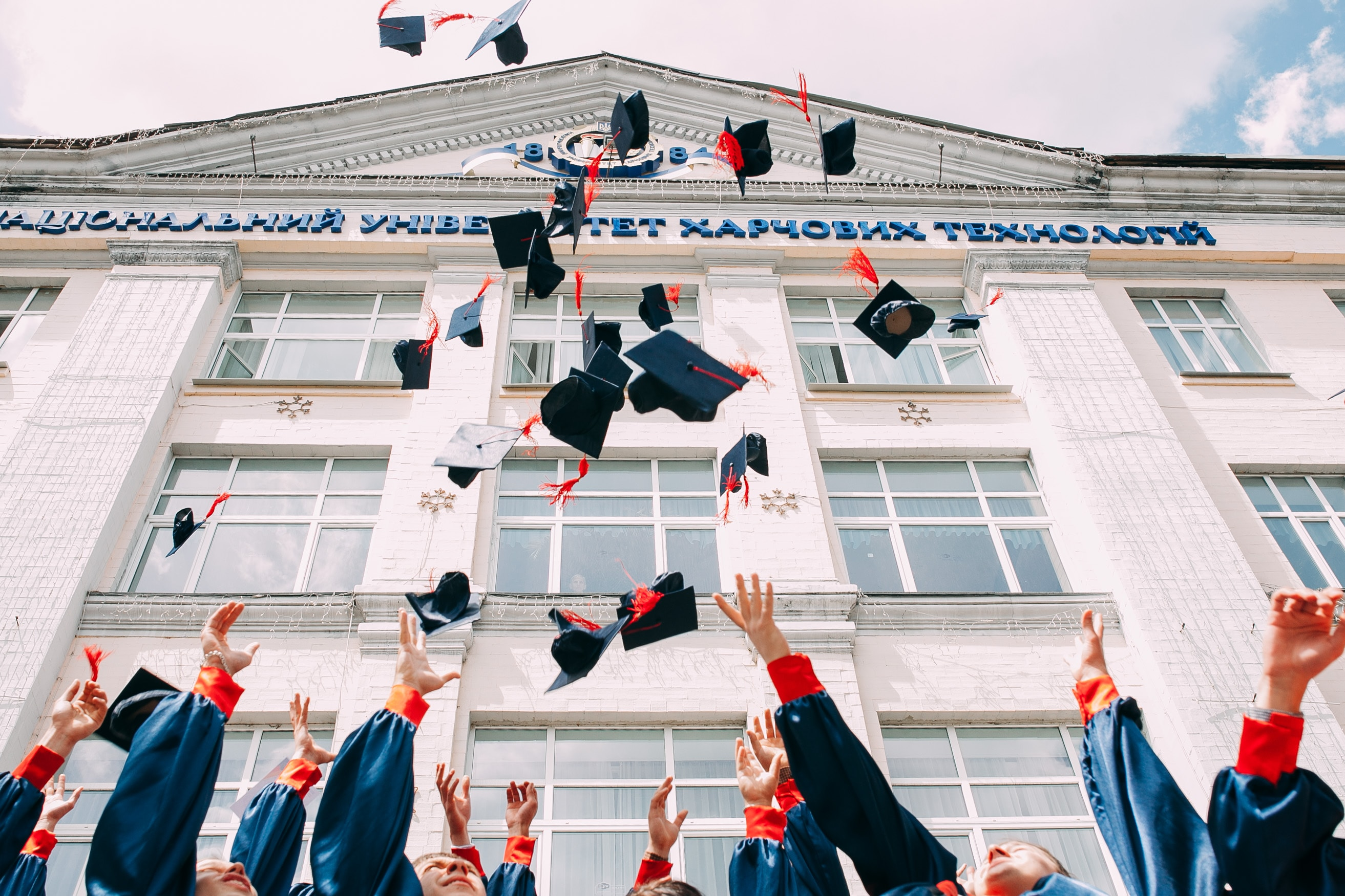 Photo of graduation caps being thrown into the air