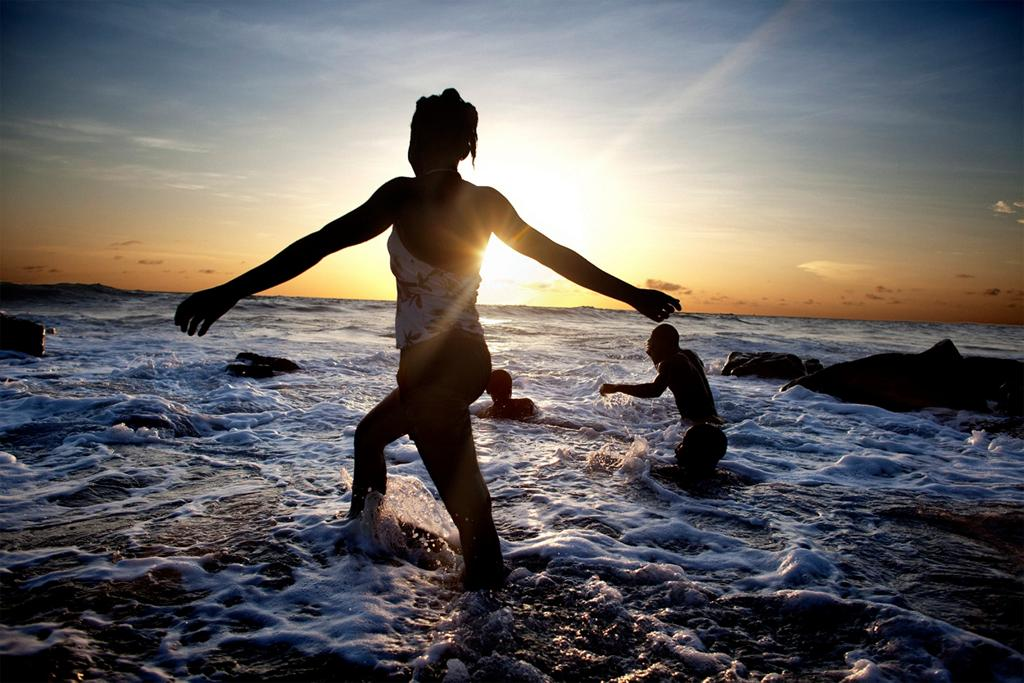 silhouette of young woman wading in the ocean