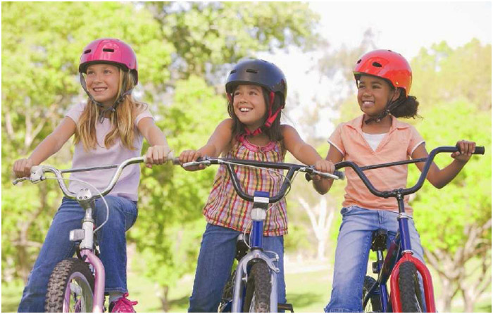 three girls wearing helmets on their bicycles