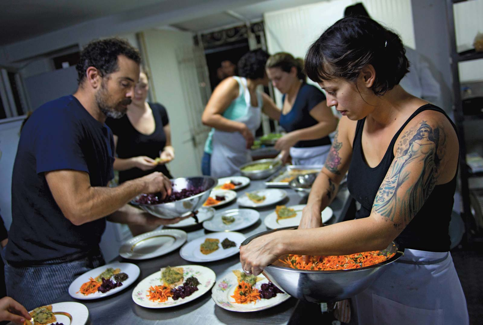 woman and man plating colorful dishes on big table
