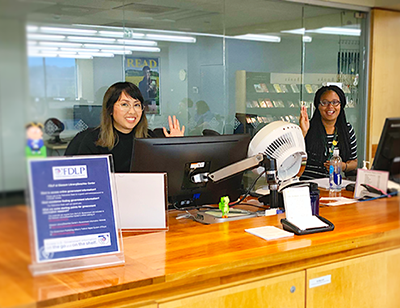 librarian and student worker at the reference desk