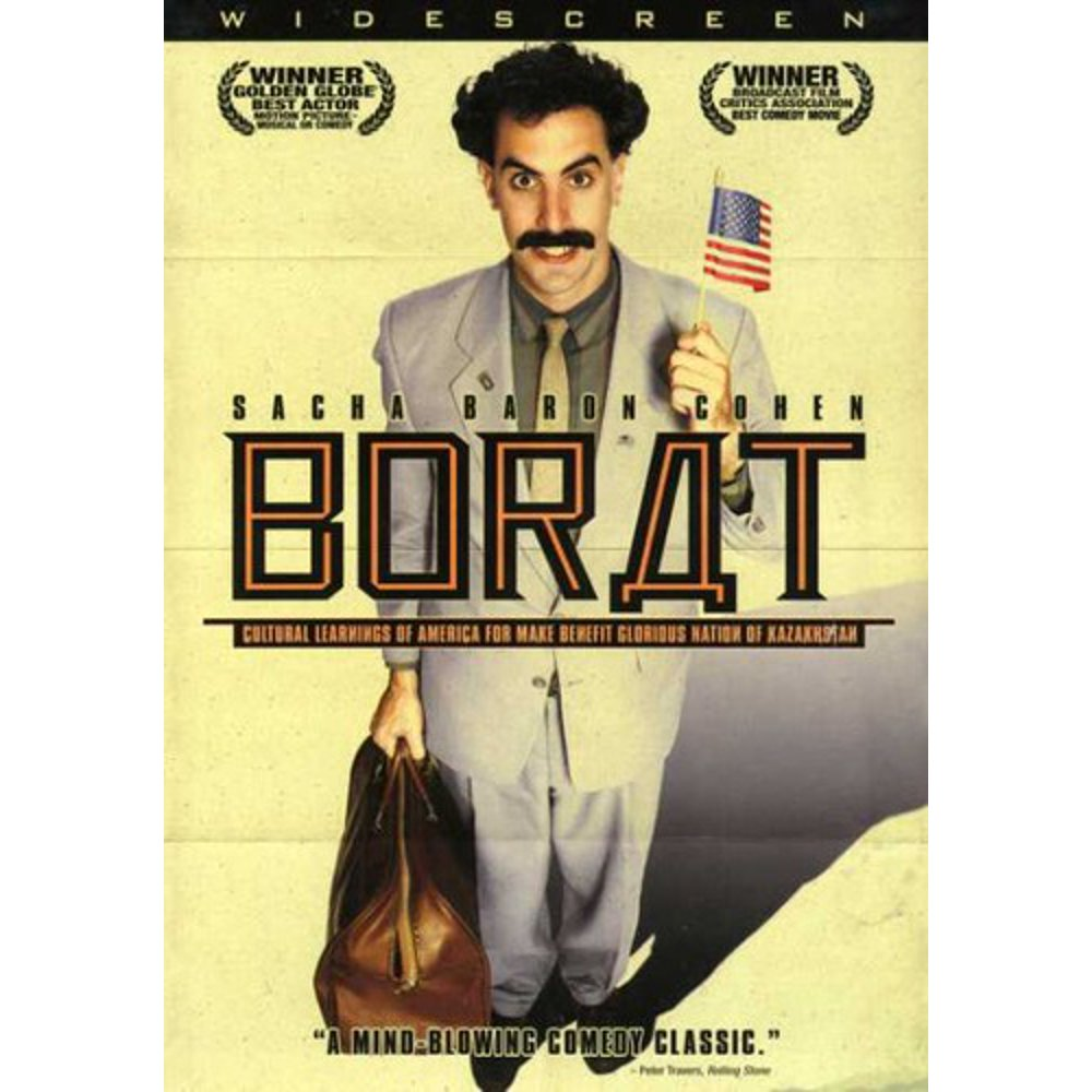 Borat in a yellow suit holding the US flag