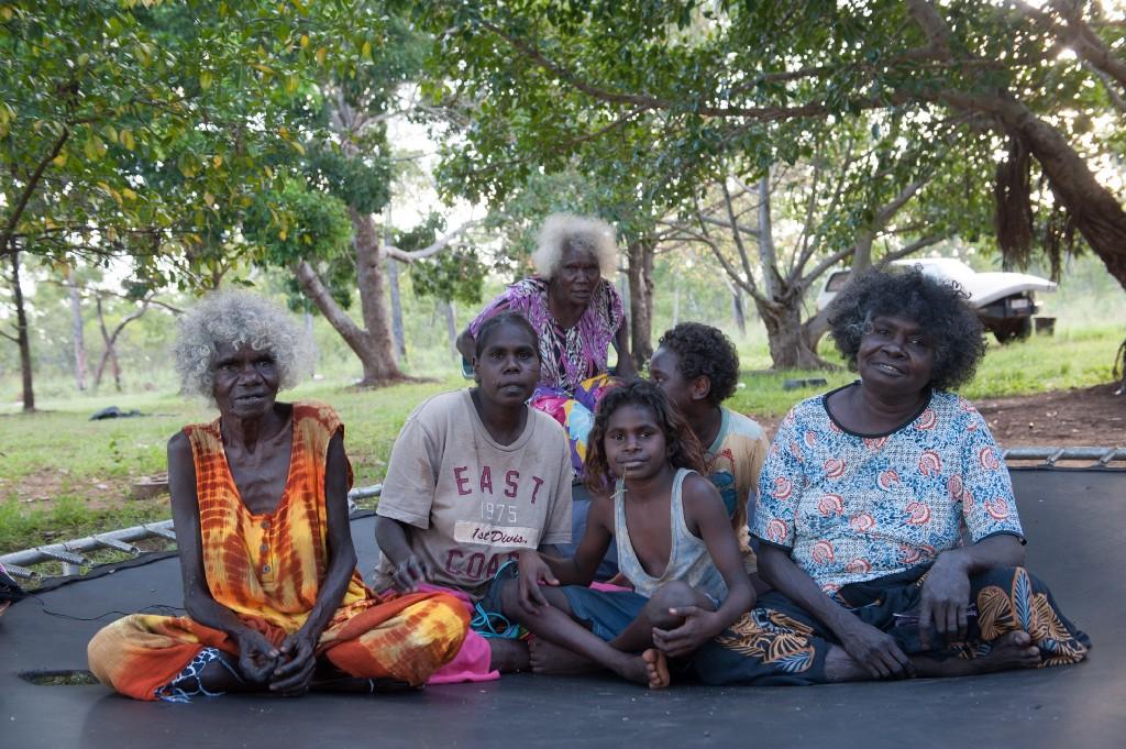 Aborigines women sitting on a blacktop road