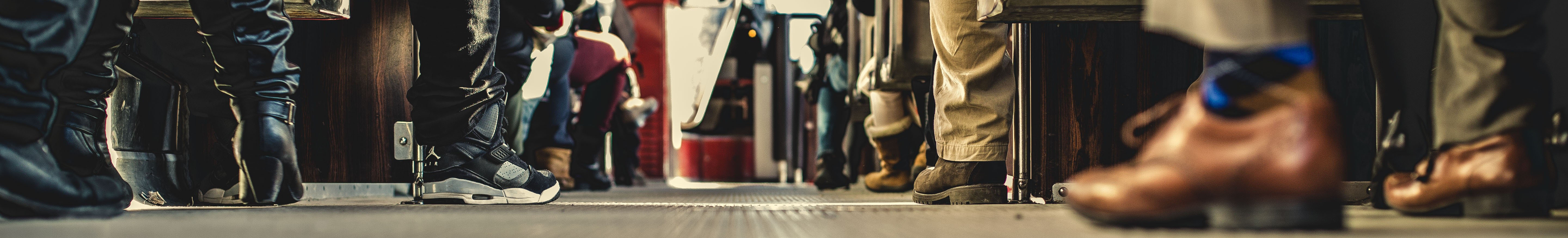 view from sitting on the back of a public bus looking forward seeing only peoples shoes. Chosen to represent people from all walks of life. Photo by Matthew Henry on Unsplash